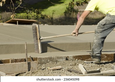 Concrete construction contractor using a broom to install texture in a sidewalk, curb and storm drainage gutter on a new urban road street project