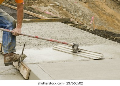 Concrete construction contractor using a float to  smooth a sidewalk, curb and storm drainage gutter on a new urban road street project