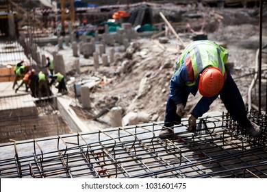Concrete construction worker, pillar, steel rebar at construction site. Contractor worker works with concrete slab steel cage. Construction site with builder worker. Concrete slab construction