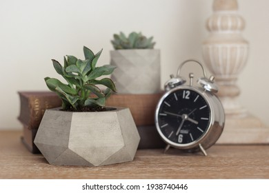 Concrete decorative flower pot and metal clock on the work table. desk layout. Decorative items on the office table. Decorative flower pot, book and clock