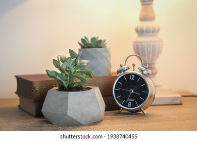 Concrete decorative plant pot and metal clock on the work table. Decorative items on the office table. Decorative flower pot, book and clock - Shutterstock ID 1938740455