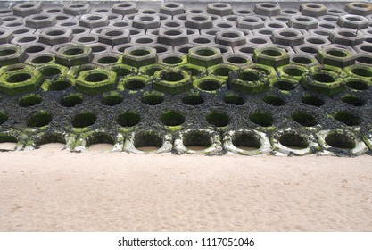 concrete defensive sea wall on a sandy beach showing seaweed on the high tide mark and the precast seabee hexagonal construction