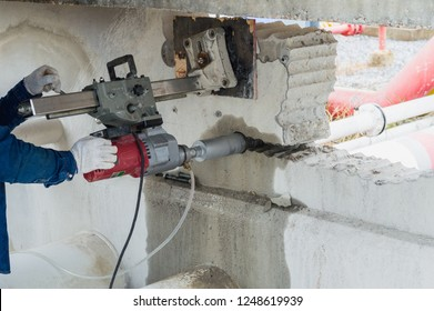 CONCRETE DRILLING MACHINE.Diamond drilling machine hole in the concrete drilling a hole in a concrete wall with a professional tool with a diamond wheel.Worker with core drill.