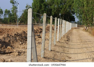 Concrete fence posts and barbed wire. Fence the farm or surveillance area to prevent intrusion or theft on the green tree background. Selective focus