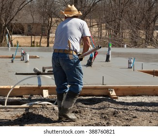 Concrete finisher uses a long handled rake to finish the surface on a residential concrete floor slab.