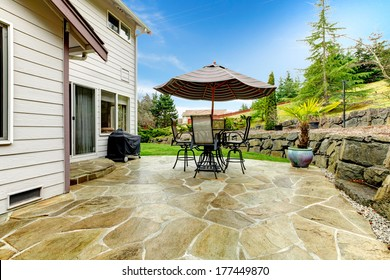 Concrete floor cozy patio area with iron table set and patio umbrella. Patio area surrounded by green terrace landscaping