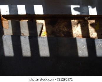 Concrete floor and dirty black stained groove, horizontal, window slot sunlight shade and shadow diagonal line stripe pattern, dry fallen leaves