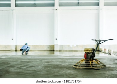 Concrete Floor Grinding Machine and Construction worker in background.