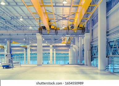 Concrete floor inside factory or warehouse building with empty space for industry background. Overhead crane or bridge crane include hoist lifting for transportation, manufacturing, and production.