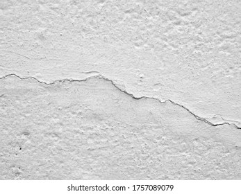 concrete floor or wall painted white with cracks are long crooked line, earthquake effect causes ground and building wall to damaged, abstract texture background, close up top view with copy space