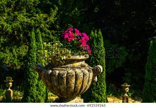 Concrete flower pots in the garden on a pedestal stylized antique, a place of rest, practical urban, flowerpot