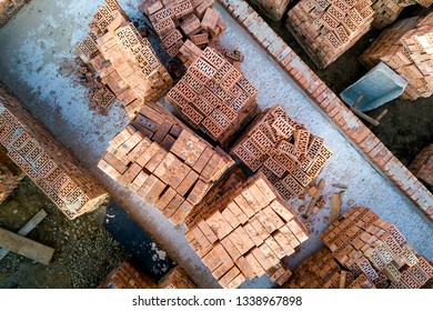 Concrete foundation of basement or first floor of future house with stacks of red bricks for walls construction on sunny summer day, aerial view.