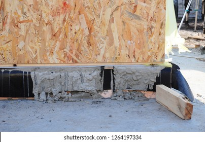 Concrete foundation with bitumen waterproofing and rigid foam insulation for wooden frame house wall.