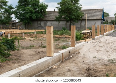 Concrete foundation for fence. Production of the concrete base for a wooden fence.