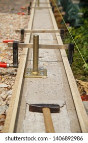 concrete foundation and form work. Clamp tool to join planks for a form base. A concrete foundation to build a carport. Pier block or Hot Dipped Galvanized post base with concrete base in ground.
