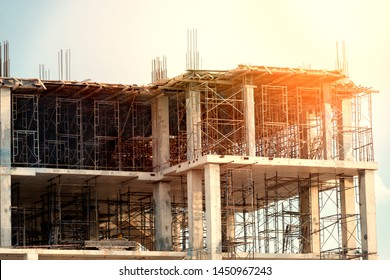 Concrete foundation of high rise building with steel scaffolding at sunset,no worker low angle view.Construction site ,shallow depth of field.