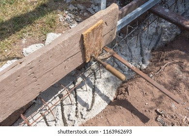 Concrete foundation with iron reinforcement and wooden formwork