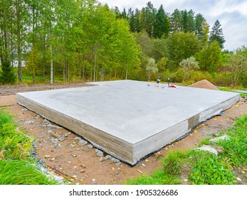 Concrete foundation next to trees. Construction near forest. Construction site with foundation. Foundation as a symbol of construction of a cottage. Building of a country cottage.