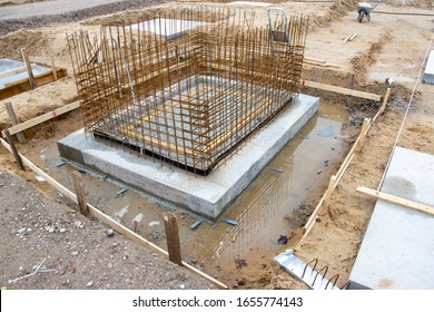 The concrete foundations for the columns of a factory building are poured on a large construction site
