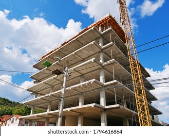 Concrete frame structure of a new multi-story apartment building in construction and crane