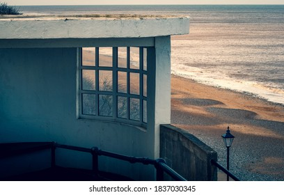 A concrete and glass lookout shelter overlooking the sandy beach at Cromer in Norfolk, UK