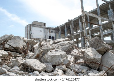 Concrete gray debris close-up on the background of the remains of the destroyed building against the sky. Background.