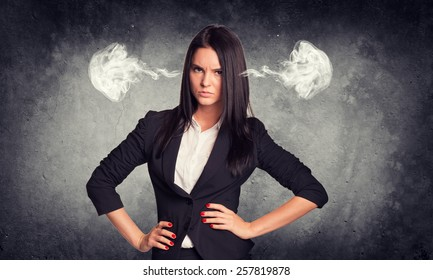 Concrete gray wall with fissure. Wicked woman in suit with steam from ears