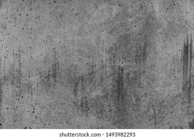 Concrete grey wall with stains and cracks