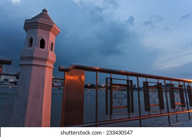 Concrete and iron fence beside river with sky at night with copy space.
