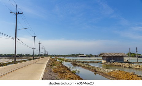 Concrete local road with electric pole in the left and canal , small cottage salt field in the right with blue sky in Thailand
