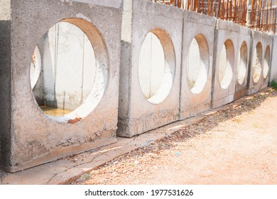 A concrete manhole prepared for use in drainage work. The large circular holes in the concrete manhole are intended for water pipes. A concrete manhole arranged in a row. Large concrete manholes.
