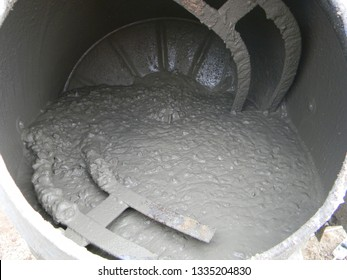 Concrete mixer with pouring cement. Close up on concrete mixer, cement mortar mixing.
