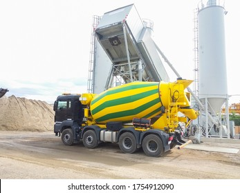 Concrete mixer truck in front of a concrete batching plant, cement factory