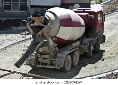 Concrete mixer truck, transport and combine cement and water in revolving drum. Worksite outdoor, heavy equipment machinery for heavy industry. Construction and renovation concept.