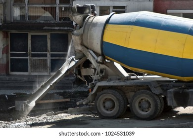 Concrete mixer yellow and blue truck, transport and combine cement and water in revolving drum. Worksite outdoor, heavy equipment machinery for heavy industry. Construction and renovation concept.