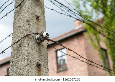 Concrete pillar for electric barbed wire in front of barracks  in former concentration camp in Auschwitz, Poland
