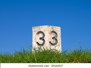 concrete pillar with the number 33 on sky background