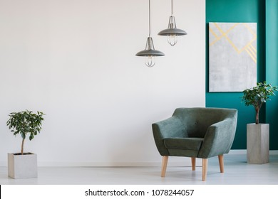 Concrete planters, industrial chandeliers and a dark, modern armchair in a minimalist living room interior