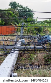 Concrete pole broken, The electric pole fell and leaned against the fence,  transformer on a electric poles and a tree laying across power lines over a road after storm.