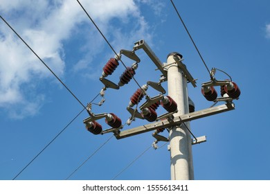 Concrete pole with high voltage three phase power line wires hanging on ceramic isolators