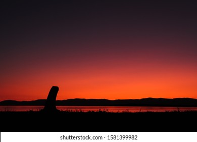 Concrete pole sihouette in sunset with river and mountain at golden hour. Saint Lawrence river. Qc. Canada