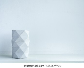 Concrete pot. Modern geometric concrete planter on white wooden shelf isolated on white background with copy space.