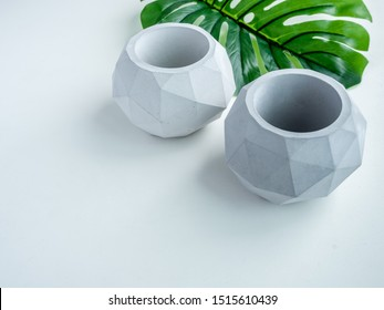Concrete pot. Top view of two empty modern geometric concrete planters with green tropical palm leaf isolated on white background with copy space.