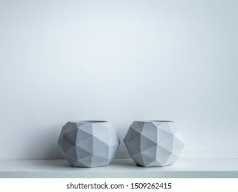 Concrete pot. Two modern geometric concrete planters on white wooden shelf isolated on white background with copy space.