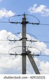 Concrete power pole against a blue sky close-up