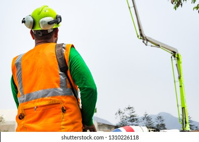 Concrete pump operator with remote control for boom pump truck at construction site.