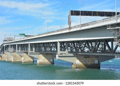 Concrete pylons and steel structure of Auckland Harbour Bridge over Waitemata Harbour from Curran Street on sunny day.