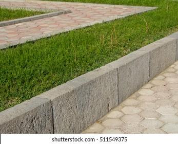 Concrete retaining wall, lawn and concrete hexagon tiles