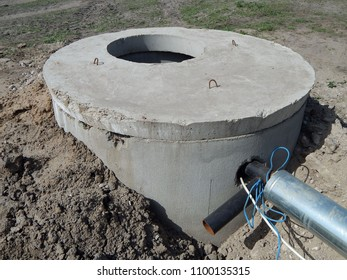 Concrete rings. Artesian well. Water swings from the ground through the pipe with the help of a pump.