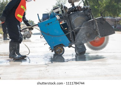Concrete Road Cutters with worker when raining over the sand truck blurred background, constructor building concept
